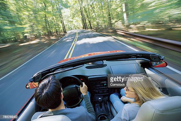 Couple driving convertible