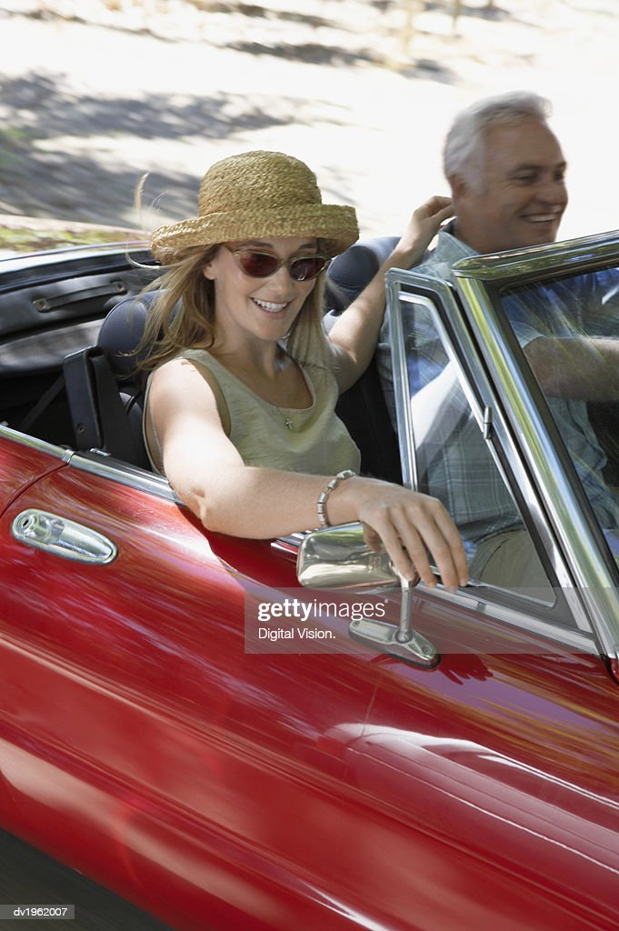 Couple Driving in a Red Convertible : Stock Photo