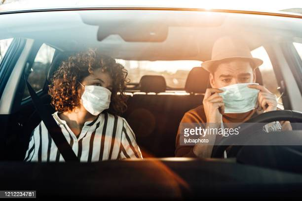 couple driving in car, travelling together, wearing hygienic mask to prevent the virus - driving mask stock pictures, royalty-free photos & images