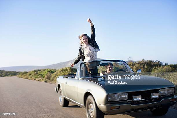 couple driving in convertible - three quarter front view stock pictures, royalty-free photos & images