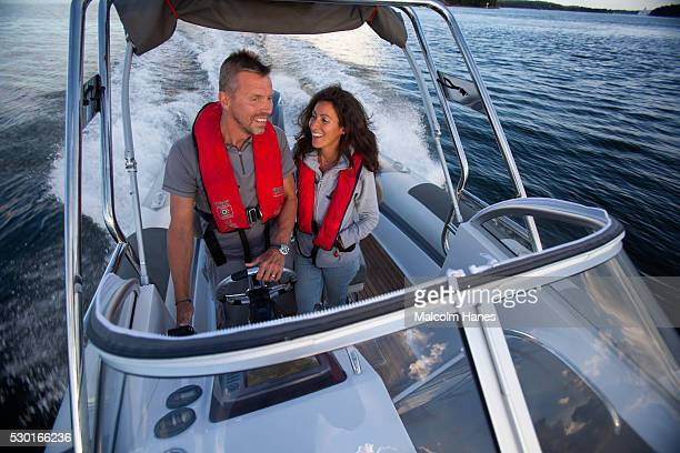 Couple driving motorboat
