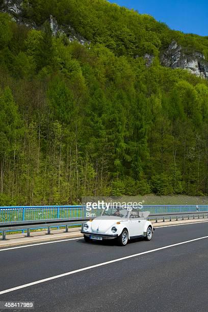 Paar fahren Vintage VW Käfer-Cabrio-Tal in den Frühling