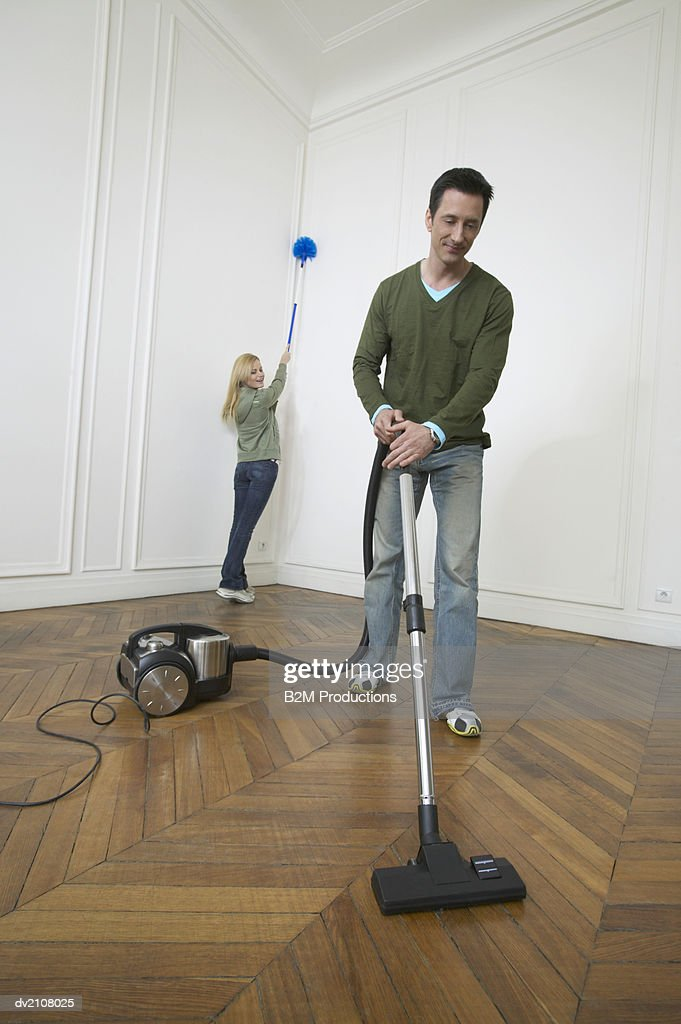 Couple Dusting and Vacuuming in a Large Empty Room with Wooden Floors : Stock Photo