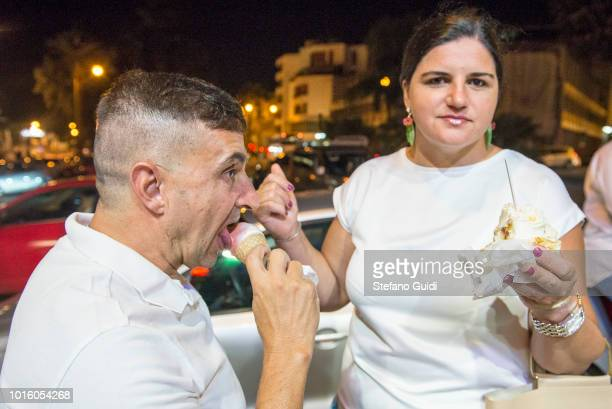 A couple eat ice cream in front of the Cesare ice cream shop during the nightlife in the Via Marina The Via Marina of Reggio Calabria consists of the...