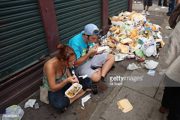 A couple eat street food next to a heap of litter on the family day at the Notting Hill Carnival on August 26 2012 in London England The annual 2day...