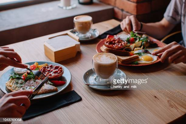 Couple eating an egg and bacon breakfast