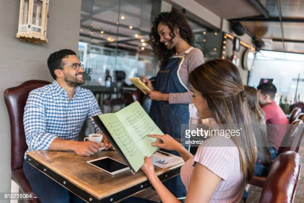 couple eating at a restaurant and checking the menu - menu stock pictures, royalty-free photos & images