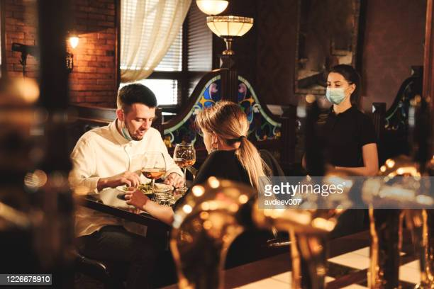 couple eating at bar reopening after quarantine restriction - restaurante imagens e fotografias de stock