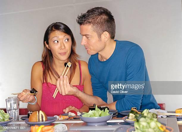 Couple eating at sushi bar