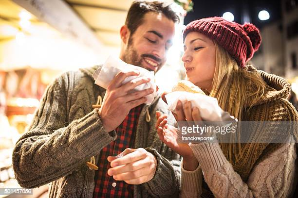 couple eating at the christmas market - man eating woman out stock photos and pictures