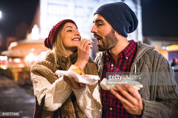 Pareja comiendo en el mercado navideño