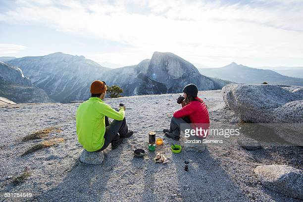 A couple eating breakfast at camp.