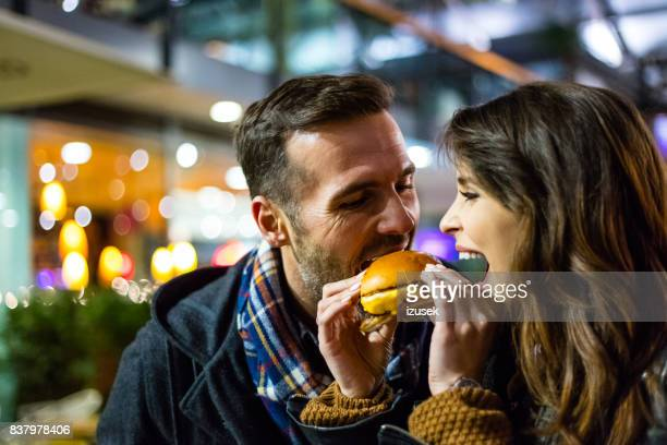 Couple eating burger together in evening