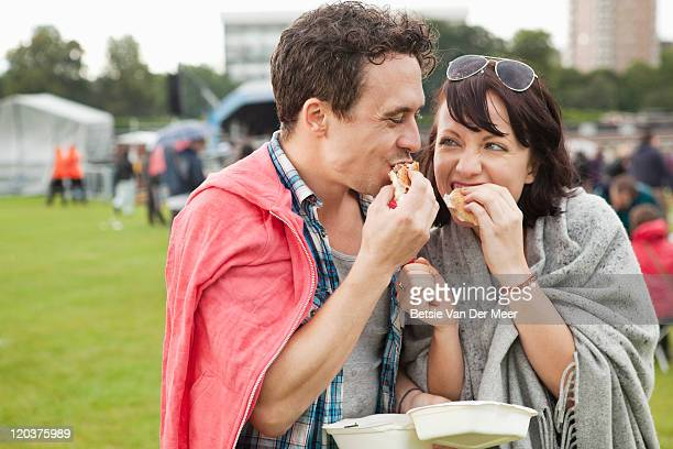 couple eating burgers at festival.