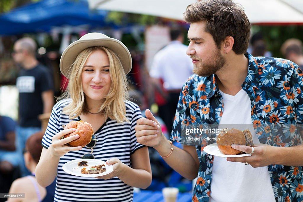 Couple eating burgers at food market : Stock Photo