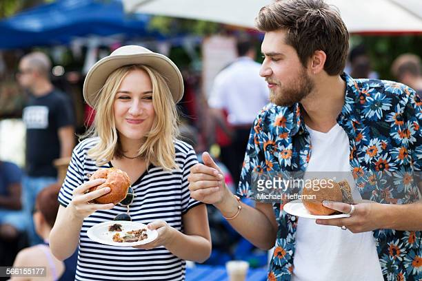 couple eating burgers at food market - daten stockfoto's en -beelden