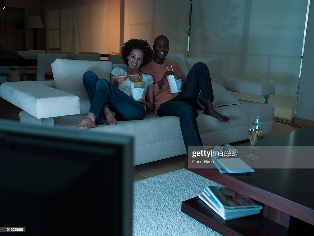 A couple eating Chinese food watching television : Stock Photo