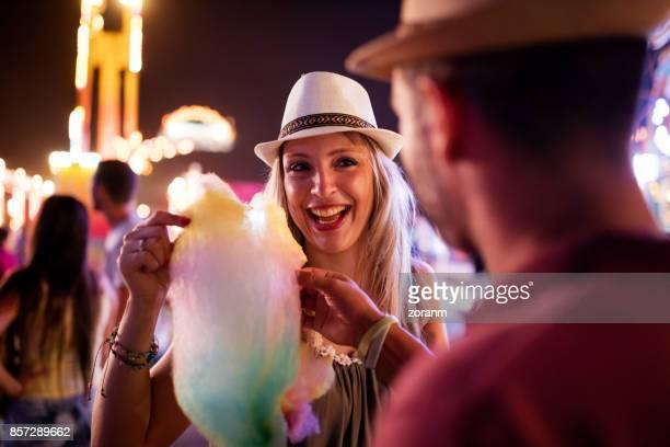 Couple eating cotton candy at amusement park