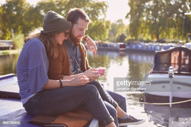 Couple eating cupcakes on canal boat