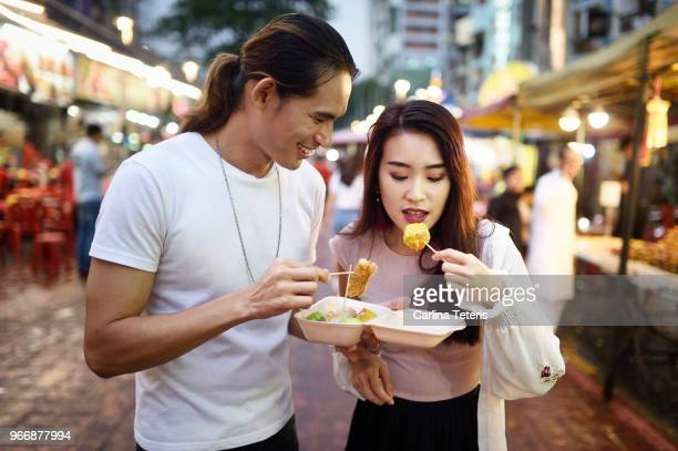 couple eating dumplings at a night market - malaysian culture stock pictures, royalty-free photos & images