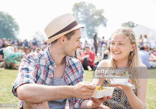 Couple eating food at outdoor festival