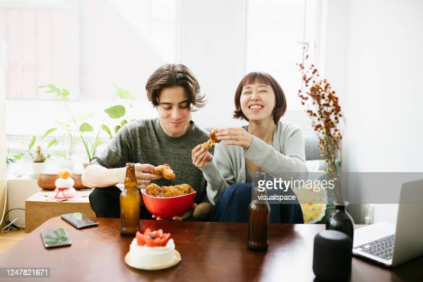 couple eating fried chicken and having a beer - japan stock pictures, royalty-free photos & images