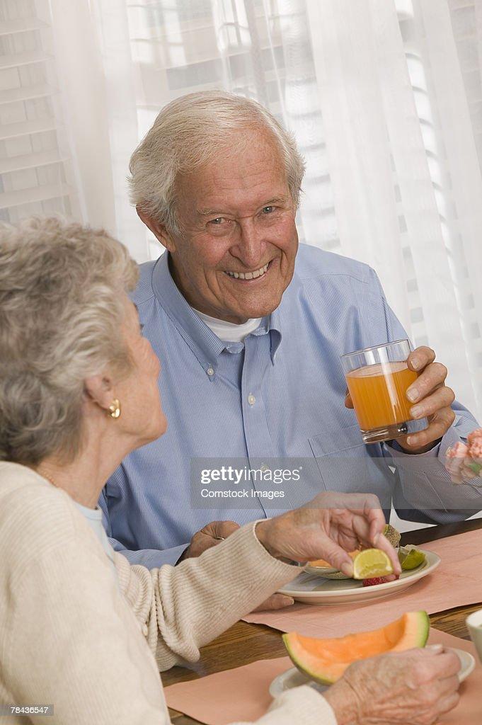 Couple eating fruit and drinking juice : Stockfoto
