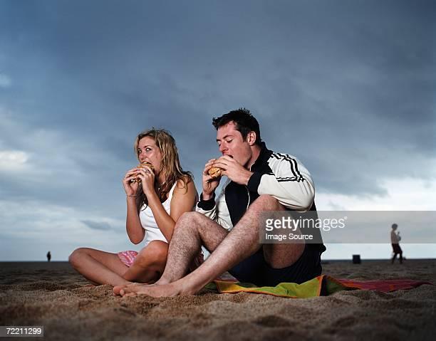 Couple eating hamburgers on beach