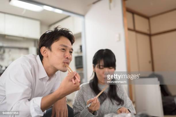 リビング ルームで一緒に食べるカップル - 食事 ストックフォトと画像