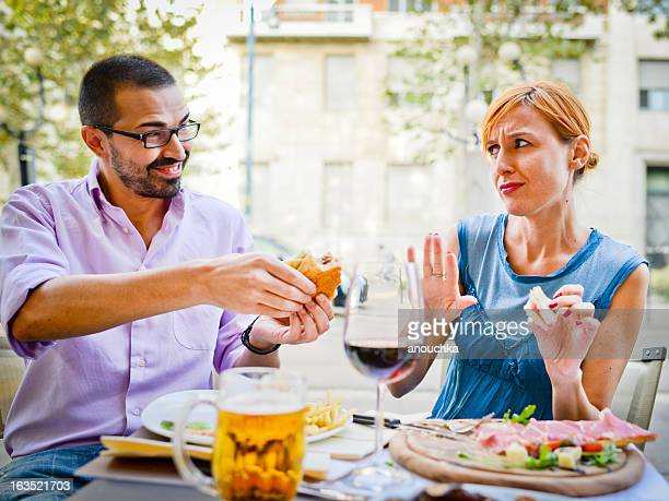 couple eating in outdoors cafe: woman refuses to eat burger - weigeren stockfoto's en -beelden