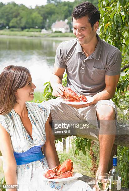 Couple eating lobster on deck