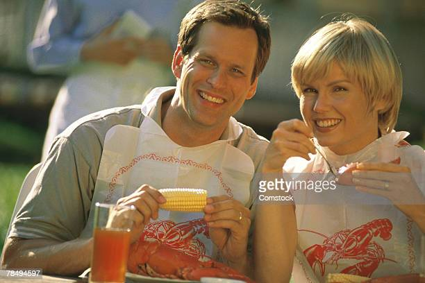 Couple eating lobster outdoors