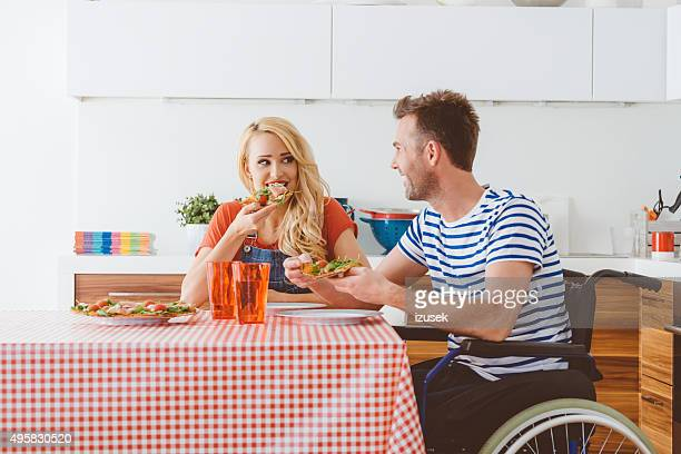 Couple eating lunch at home, disabled man sitting in wheelchair