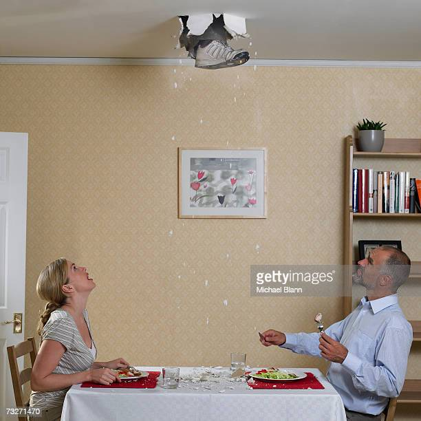 couple eating meal with foot coming through ceiling - ceiling stock pictures, royalty-free photos & images