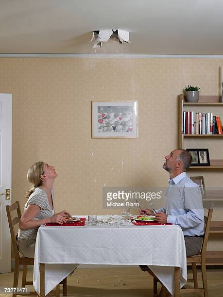 Couple eating meal with hole in ceiling