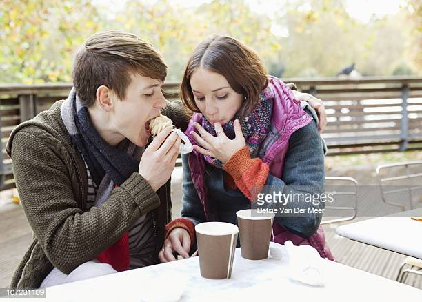 Couple eating muffins in park cafe.