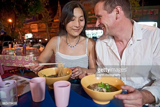 couple eating noodle soup at Thai open air market