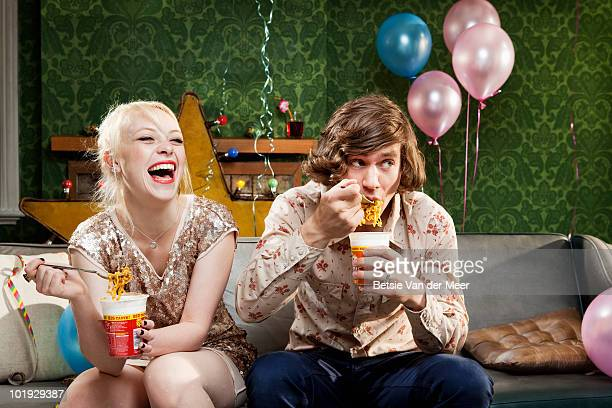 couple eating noodles on sofa.