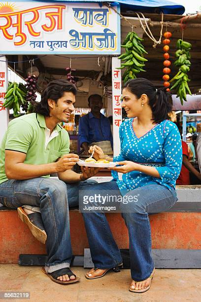 Couple eating pau bhajji, India