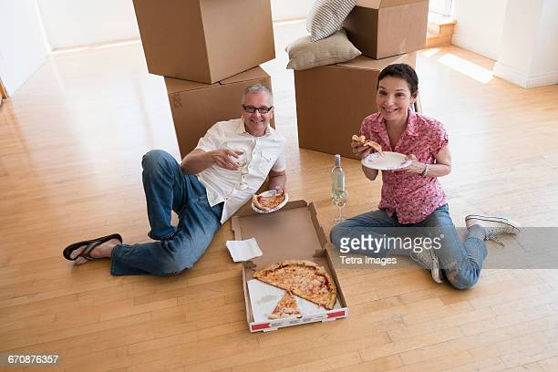 Couple eating pizza in new apartment