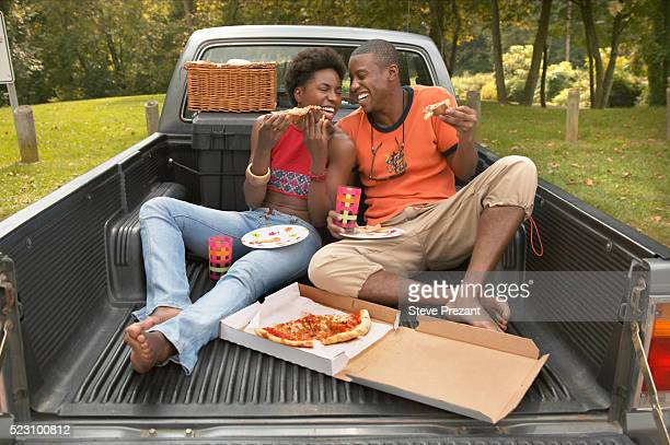 Couple Eating Pizza in Pickup Bed