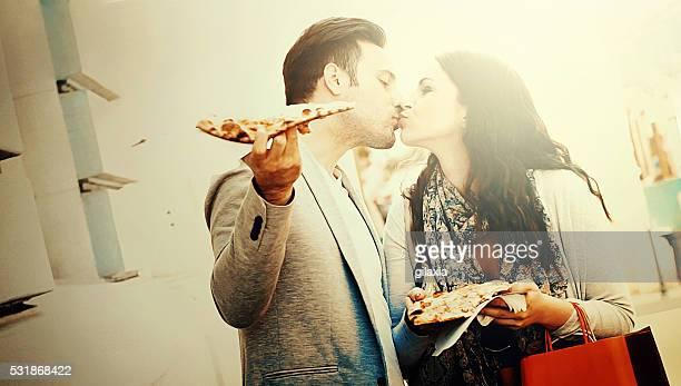 Casal a comer pizza na rua.