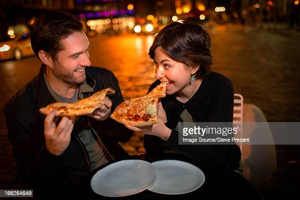 Couple eating pizza on city street