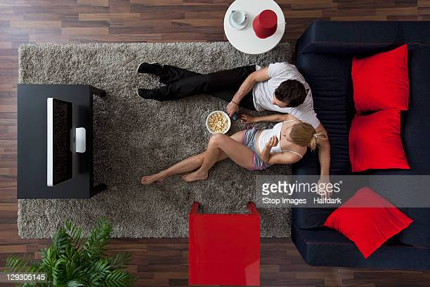 a couple eating popcorn and watching tv in their living room, overhead view - arts culture and entertainment stock pictures, royalty-free photos & images