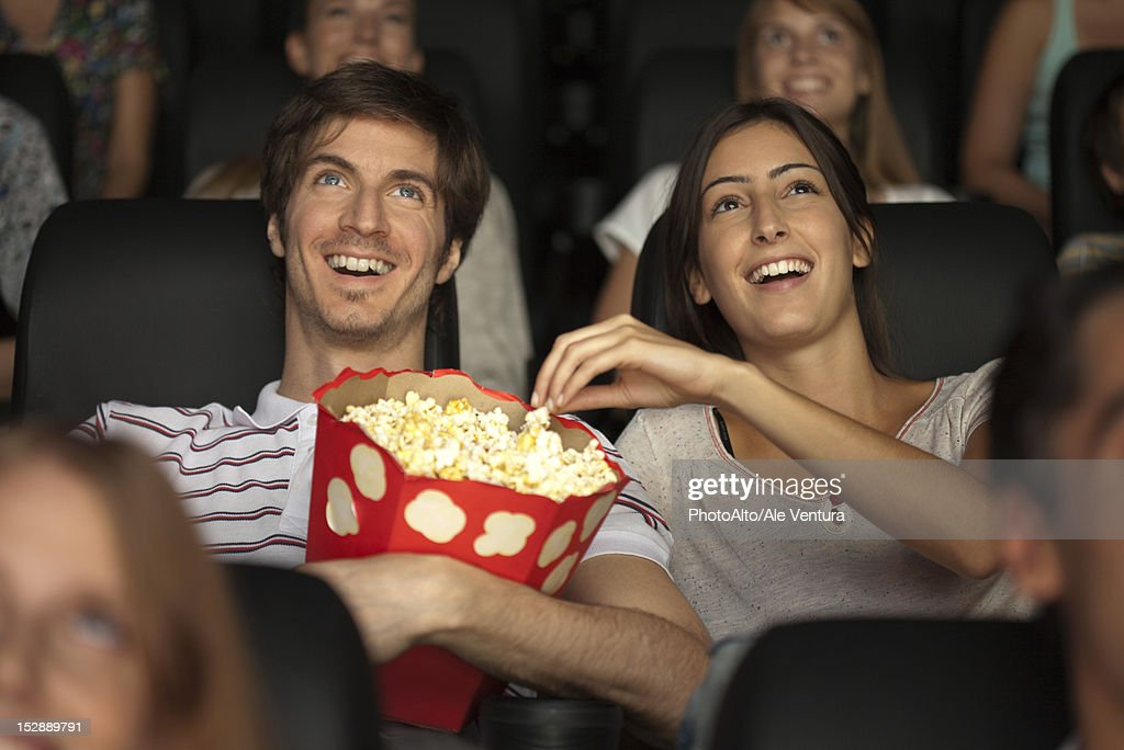 Couple eating popcorn in movie theater : Stock Photo