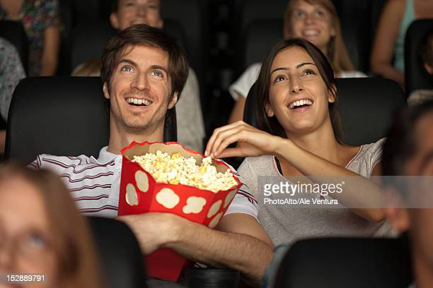 Couple eating popcorn in movie theater
