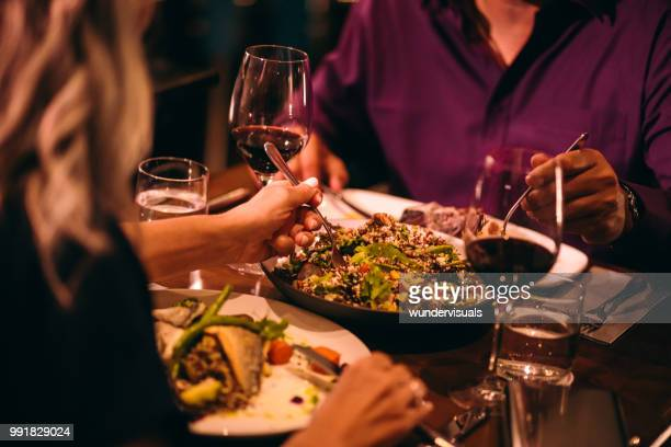 couple eating quinoa salad and healthy dinner at restaurant - romanticism stock pictures, royalty-free photos & images