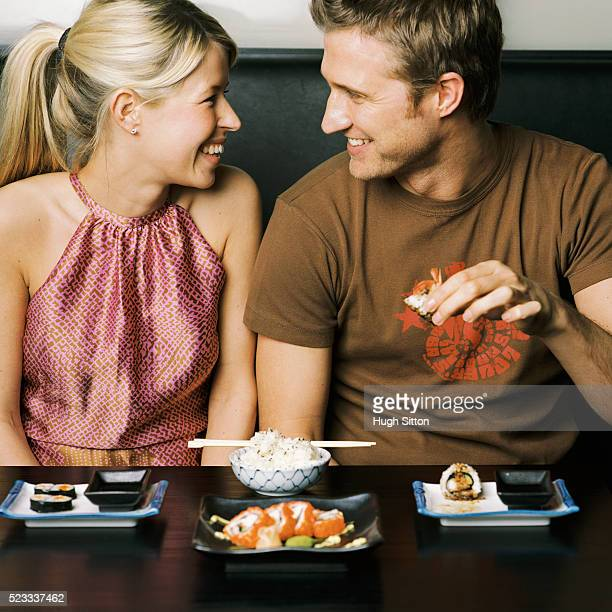 couple eating sushi - hugh sitton stock pictures, royalty-free photos & images
