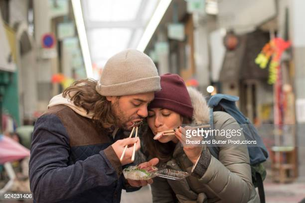 Couple Eating Sushi Together with Chopsticks in the Dotombori district, Osaka, Japan