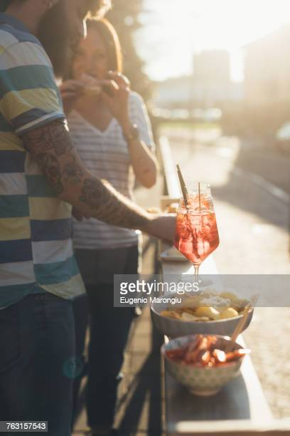 Couple eating tapas at sunlit sidewalk cafe